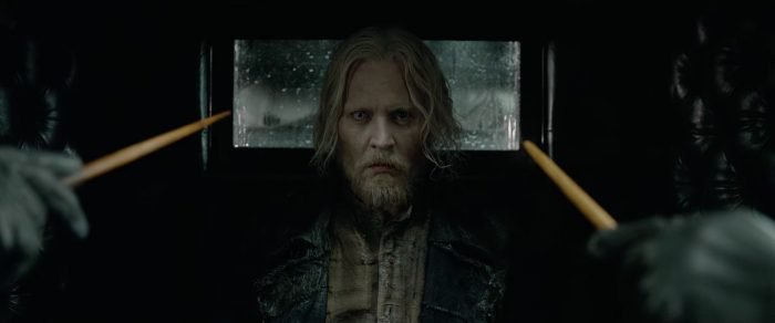 Johnny Depp, as Grindelwald, with wands pointed at him.